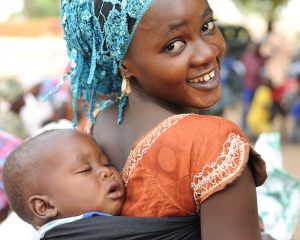African women with a sleeping child on her back