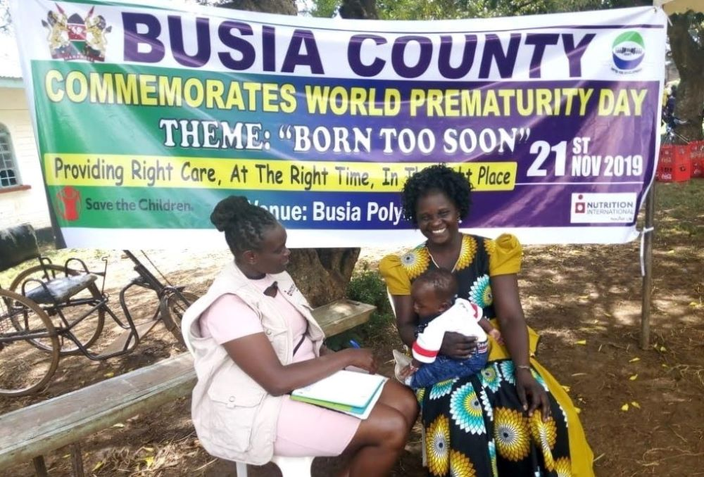Roselyn with health worker and baby