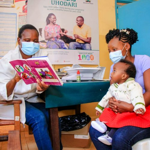 Purity and baby Ashley speak to a health worker at Mbeere health facility